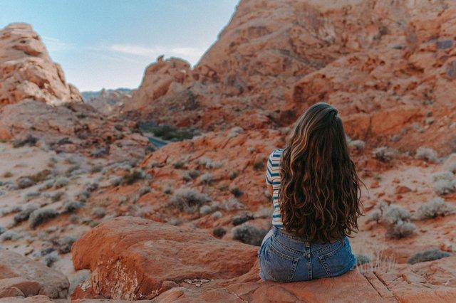 woman-in-blue-denim-shorts-sitting-on-brown-rock-mountain-3935704.jpg